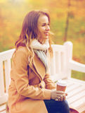 Happy young woman drinking coffee in autumn park. Season, hot drinks and people concept - beautiful happy young woman drinking coffee or tea from disposable Stock Image