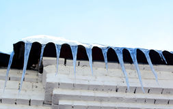 Season, housing and winter concept - icicles hanging on facade r Stock Photo