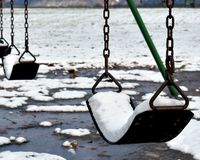 Snow filled swings stock images