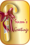 Season's Greetings. Silver and gold striped candy cane with a red bow. Gold background with the message 'Season's Greetings' in red Stock Photos