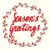 Season's Greetings calligraphy. Christmas floral frame. Christmas card. Royalty Free Stock Photo