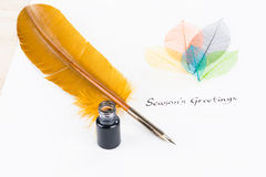 Season`s Greetings message on cotton paper and quill pen Stock Images
