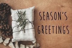 Season`s greetings text sign on stylish christmas rustic gift wrapped in linen fabric with green branch on wood with pine cones. royalty free stock photos
