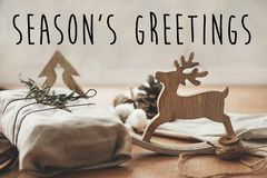 Season`s greetings text sign on stylish christmas rustic gift wrapped in linen fabric with green branch on wood with pine cones,. Reindeer, lights.Seasonal royalty free stock image