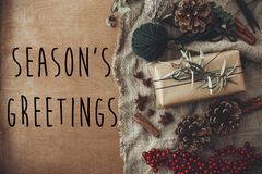 Season`s greetings text sign on stylish rustic christmas gift box with fir branches, red berries, pine cones, cinnamon on rustic royalty free stock image