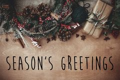 Season`s greetings text sign on stylish rustic christmas wreath, gift box with fir branches, red berries, pine cones, cinnamon on stock photography