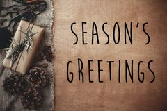 Season`s greetings text sign on stylish rustic gift box with green branches, anise, pine cones, cinnamon on rustic wood. Seasonal royalty free stock photos