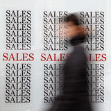 Season sales. Person passing by shop with sales signs royalty free stock photo