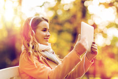 Woman with tablet pc and headphones in autumn park Stock Images
