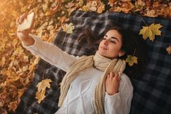 Season, technology and people concept - beautiful young woman lying on ground and autumn leaves and taking selfie with stock photography