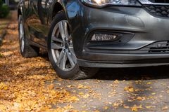 Season tire change. Car with new winter tires on the road for autumn leaves. stock photo