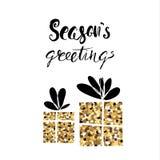 Season& x27; caligrafía manuscrita de la Navidad de los saludos de s Dos regalos del brillo de oro aislados en blanco Foto de archivo