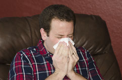 Seasonal allergies got you down?. Man blowing his nose while sitting in a brown leather chair royalty free stock photo