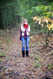 Seasonal allergy. A full length portrait of woman with allergies or flu blowing her nose standing outdoors in autumn Stock Image