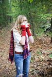 Seasonal allergy. A three quarter length portrait of woman with allergies or flu blowing her nose standing outdoors in autumn Stock Photography