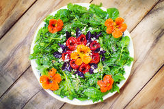 Seasonal arugula salad with goat cheese, roasted red peppers and edible nasturtium flowers. (selective focus Royalty Free Stock Photo