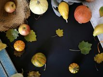 Seasonal autumn composition from a variety of pumpkins, pears, apples, yellow leaves and straw hat, preparation for a home holiday. Helloween, dark background royalty free stock image