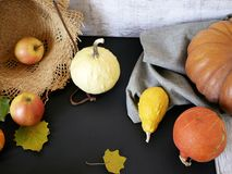 Seasonal autumn composition from a variety of pumpkins, pears, apples, yellow leaves and straw hat, preparation for a home holiday. Helloween, dark background stock photo