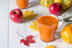 Seasonal autumn thanksgiving concept. Pumpkin fresh juice drink cocktail on a white table with fall maple leaves. Copy space royalty free stock images