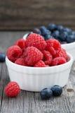 Seasonal berries - raspberries and blueberries in bowls. Seasonal berries - raspberries and blueberries, vertical, close-up Stock Image