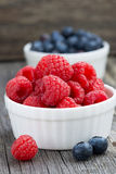 Seasonal berries - raspberries and blueberries. On wooden background, close-up, horizontal Stock Photo