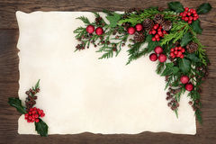 Seasonal Border. Christmas background floral border with red bauble decorations, holly, ivy, fir, cedar cypress and pine cones on parchment paper over old oak Royalty Free Stock Photos