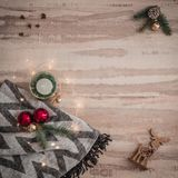 Seasonal Christmas border composed of decorative gifts, deer, candle and scarf, pine branches ornaments over a wooden background stock photography