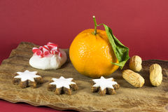 Seasonal Christmas still life home decoration. With a fresh clementine, groundnuts or peanuts, white iced star cookies and a festive meringue with candy cane royalty free stock image