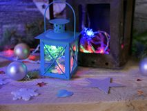 Seasonal composition of Christmas decor, decorative lanterns with Christmas tree illumination on a wooden textural background. Blue lighting, the concept of royalty free stock photography