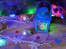 Seasonal composition of Christmas decor, decorative lanterns with Christmas tree illumination on a wooden textural background. Blue lighting, the concept of royalty free stock image
