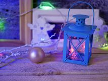Seasonal composition of Christmas decor, decorative lanterns with Christmas tree illumination on a wooden textural background. Blue lighting, the concept of royalty free stock photo