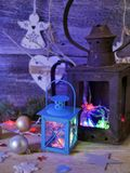 Seasonal composition of Christmas decor, decorative lanterns with Christmas tree illumination on a wooden textural background. Blue lighting, the concept of stock image