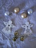 Seasonal composition of the decor of two white angels Christmas decorations, gold and silver balls on a light background top view stock image
