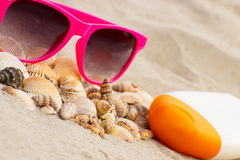 Seasonal concept, heap of shells, sunglasses and sun lotion Royalty Free Stock Photography