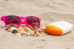 Seasonal concept, heap of shells, sunglasses and sun lotion Stock Photo