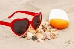 Seasonal concept, heap of shells, sunglasses and sun lotion Stock Image