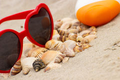 Seasonal concept, heap of shells, sunglasses and sun lotion Royalty Free Stock Image