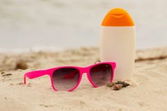 Seasonal concept, shells, pink sunglasses and sun lotion Royalty Free Stock Photo