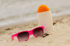Seasonal concept, shells, pink sunglasses and sun lotion Royalty Free Stock Photos