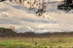 Countryside landscape with snow mountains. Seasonal countryside landscape with snow mountains in the far background royalty free stock photos