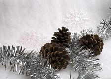 Seasonal decorations. Three pine cones in the snow blanket with some christmas ornaments stock photography