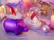 Seasonal decorative composition of burning candles, pigs, decorative lamps, festive decor on a silver background stock photo