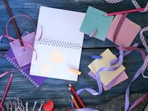 Seasonal decorative composition of leaves, hearts of felt, empty notebook, greeting paper, pencils, rose petals on a wood backgrou stock photos