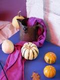 Seasonal decorative still life of pumpkins, purple fabric, black plasticine spider royalty free stock photos