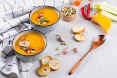 Seasonal fall autumn roasted orange pumpkin carrot soup with ingredients Royalty Free Stock Images