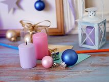 Seasonal festive interior composition of candles, Christmas decor, wooden vintage frames, decorative lamps, paper for notes on a w. Ooden table, the concept of royalty free stock photography