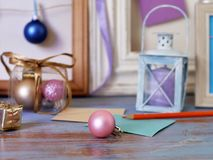 Seasonal festive interior composition of candles, Christmas decor, wooden vintage frames, decorative lamps, paper for notes on a w. Ooden table, the concept of royalty free stock image