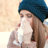 Seasonal flu. Pretty young woman blowing her nose with a tissue outdoor in winter Royalty Free Stock Photo