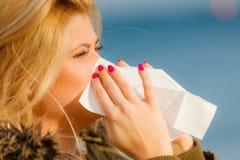 Sneezing woman into handkerchief, outside sunny shot Stock Photography