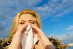 Sneezing woman into handkerchief, outside sunny shot Stock Photos